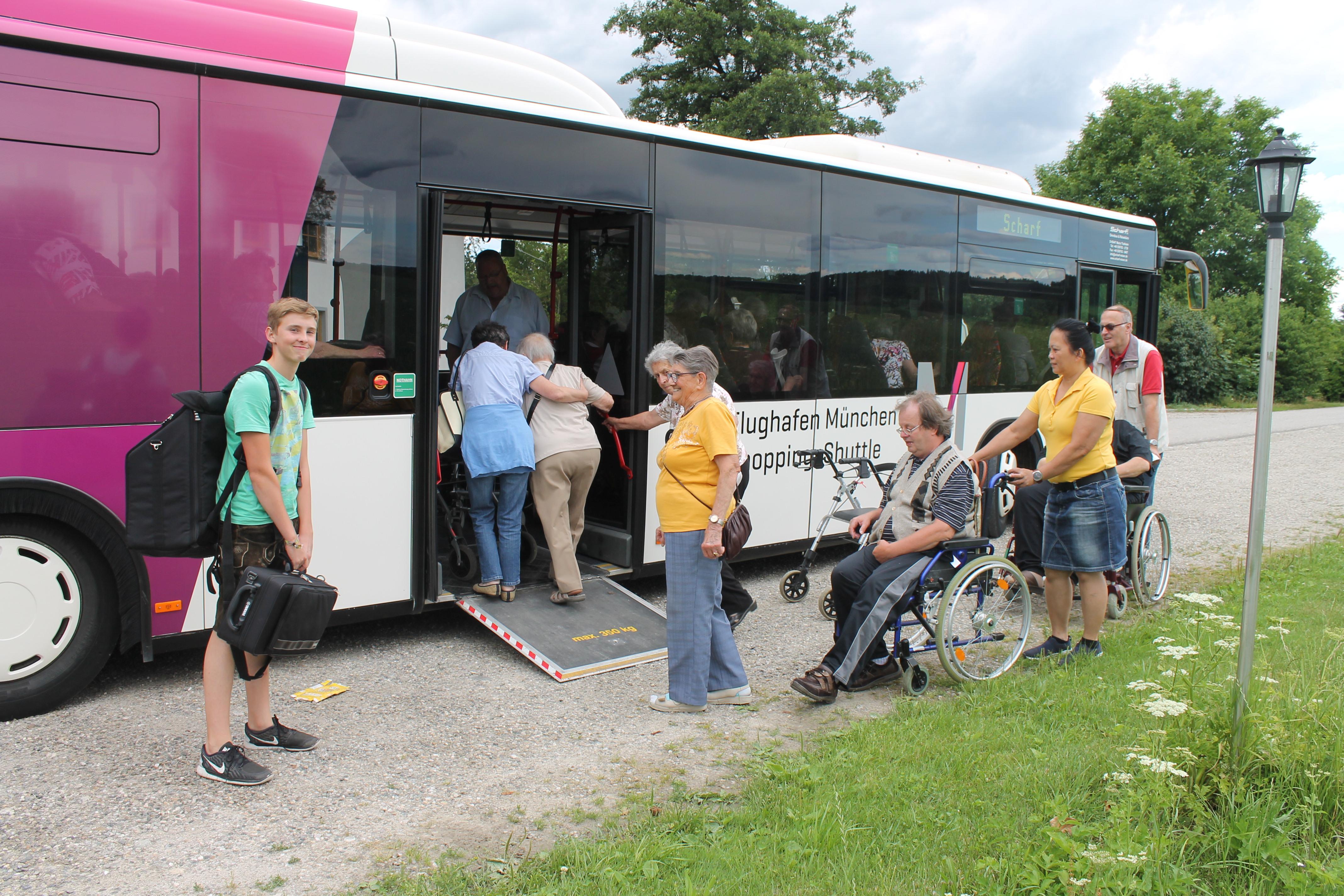 NBH-Helfer betreuten die Gäste beim Einstieg in den mit Rampe ausgestatteten Bus. Lorenz Schumertl (links), der junge Musikant